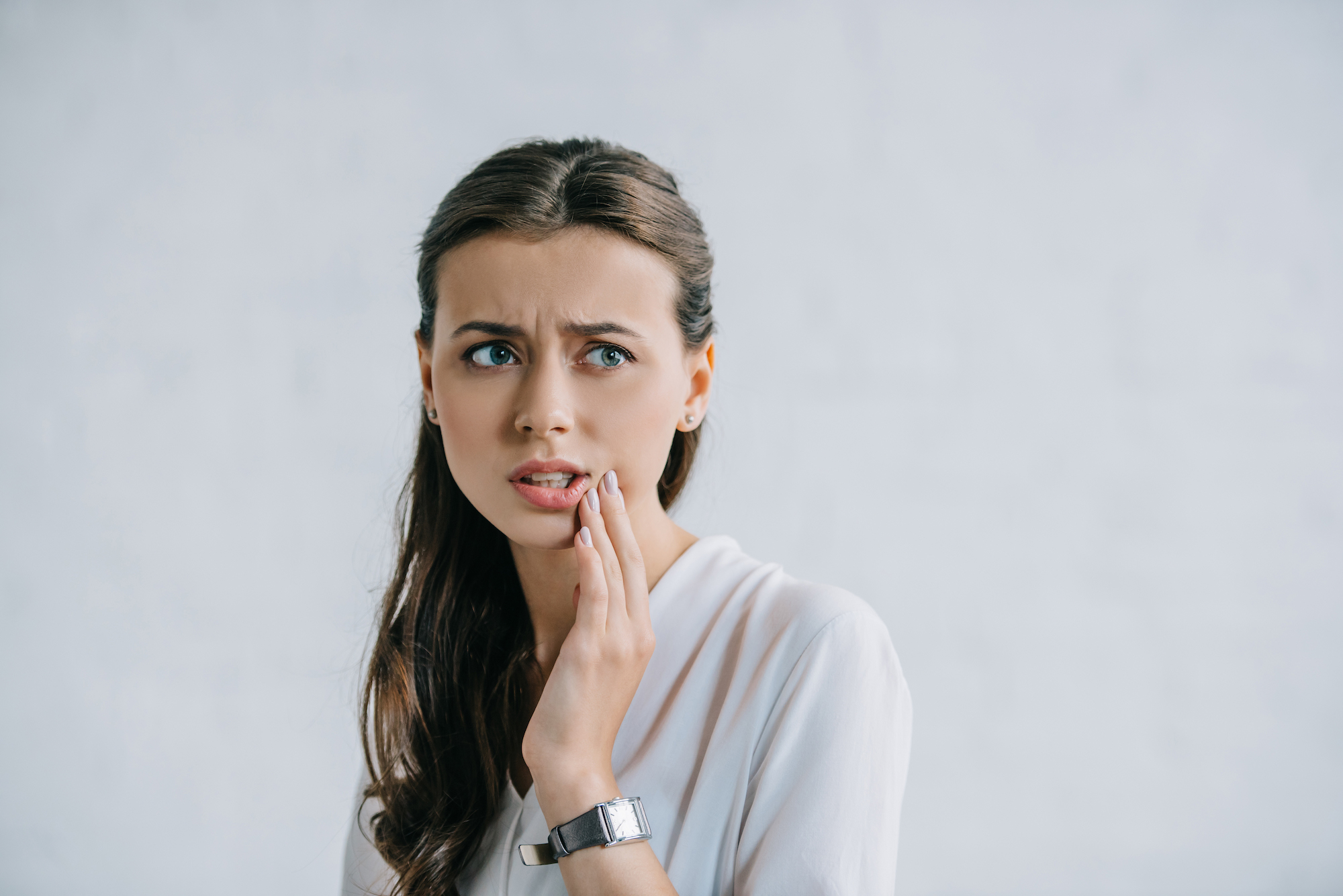 attractive young woman suffering from toothache and looking away