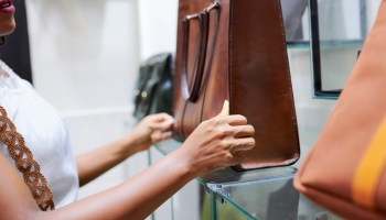 Young woman looking at big leather bag in fashion boutique