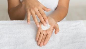 Skin nutrition. Girl spreading nourishing cream on palm against towel