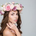 Portrait of a lovely woman with wreath from flowers on head posing over gray background