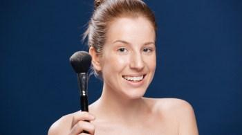 Happy woman holding makeup brush