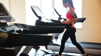 Sportswoman with earphones and blank screen smartphone using treadmill