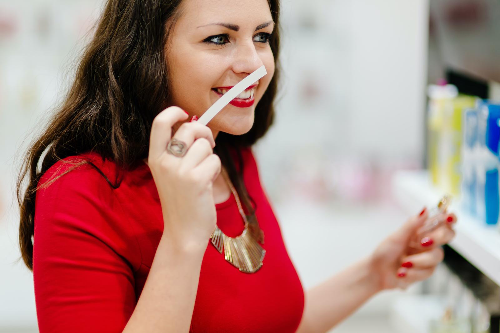 Happy woman testing new fragrances
