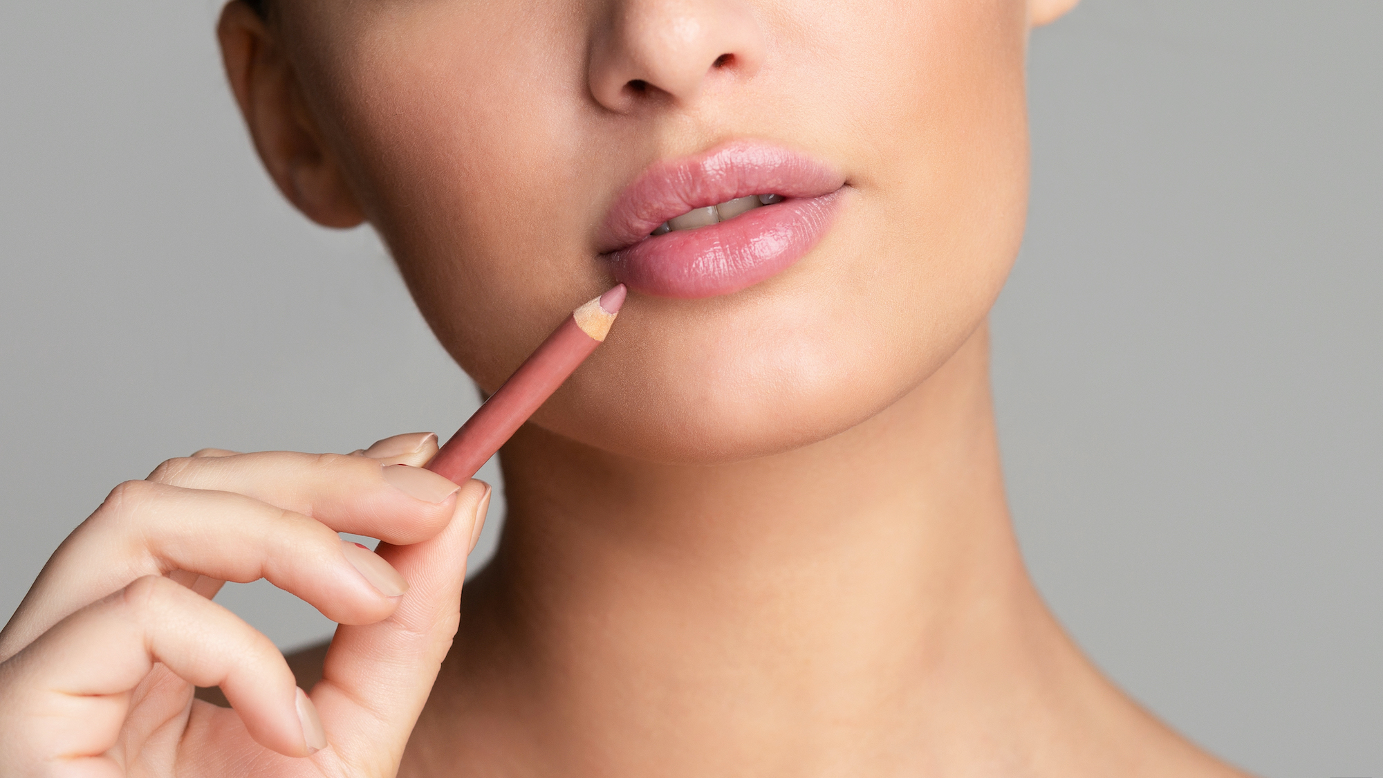 Beauty concept. Woman drawing lips with nude pink lipliner over grey background, crop