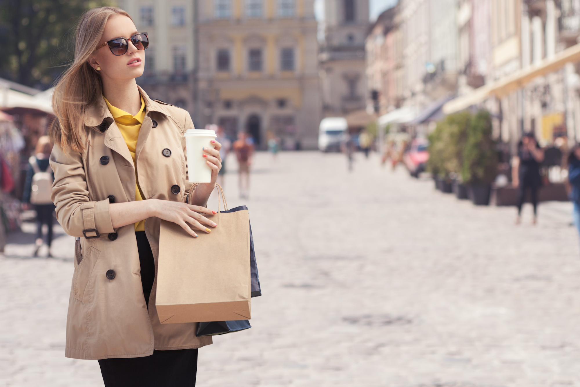 Young fashionable woman taking a coffee break after shopping, walking with a coffee-to-go in her hands against urban city background.