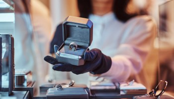 Close-up photo of a ring in open box, woman assistant shows the exclusive gold ring in the luxury jewelry store
