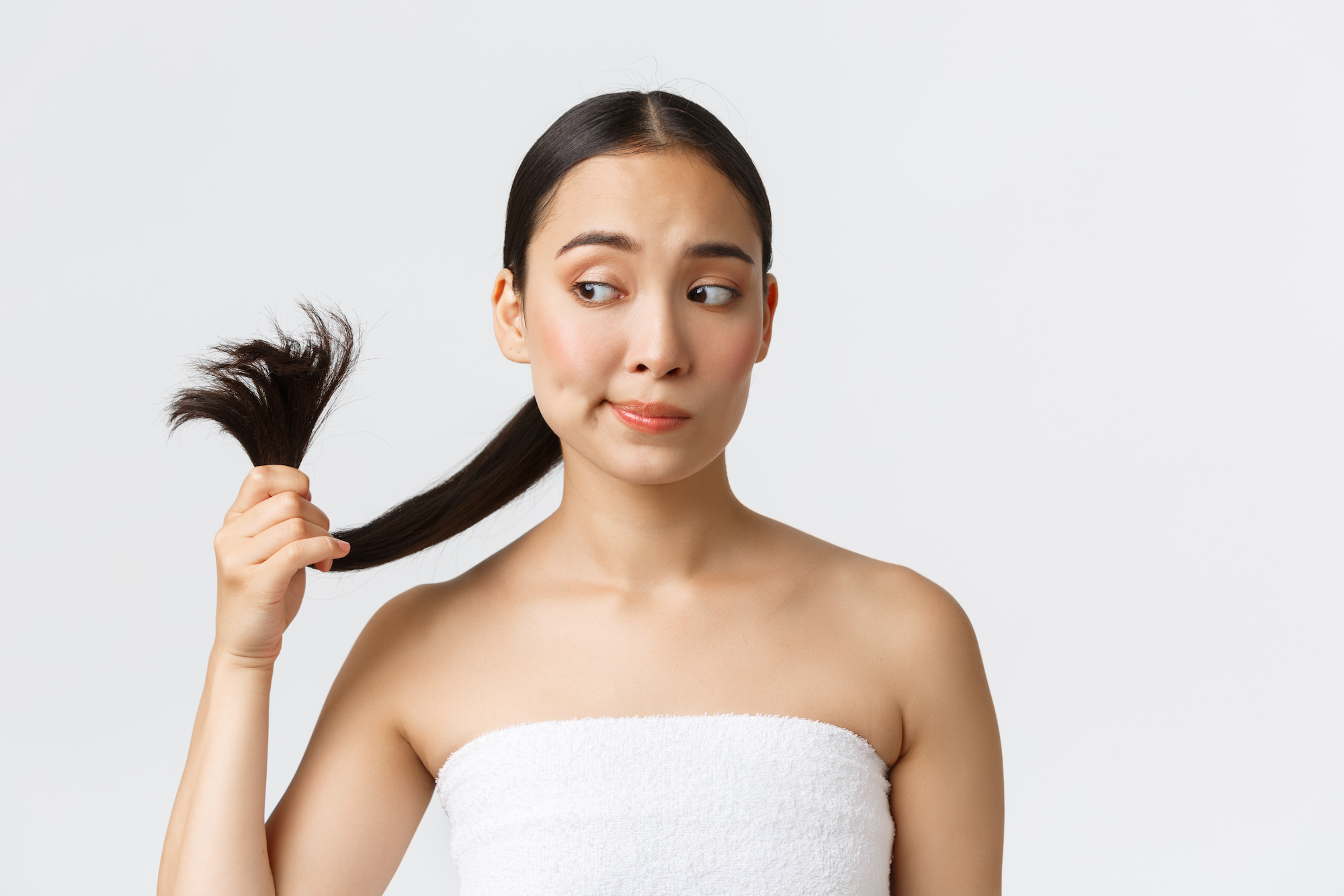 Beauty, hair loss products, shampoo and hair care concept. Troubled beautiful asian woman in bath towel looking at split ends, need hair treatment, standing white background.