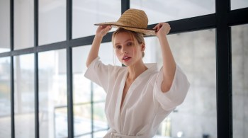 Blonde woman holding straw hat while choosing straw hat