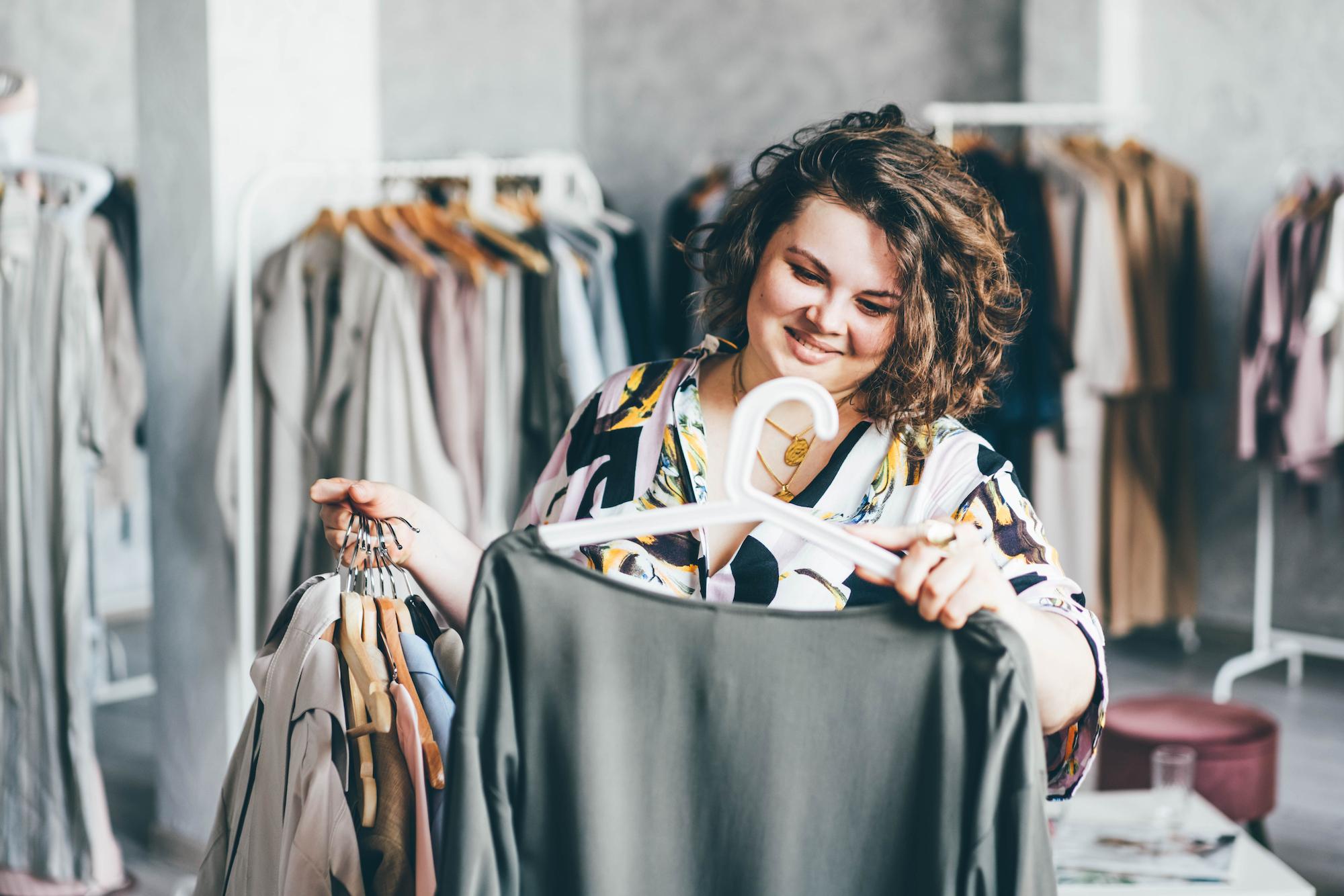 Plus Size Woman Choose Fashioned Dress in Store. Plus size women shopping.