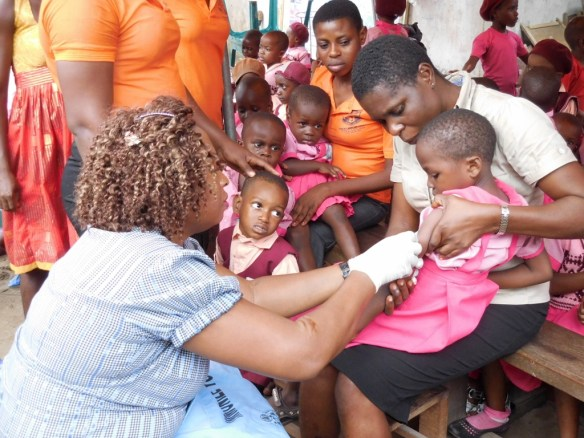 Some of our youngest Bodo students receiving typhoid shots with some of the teachers helping.
