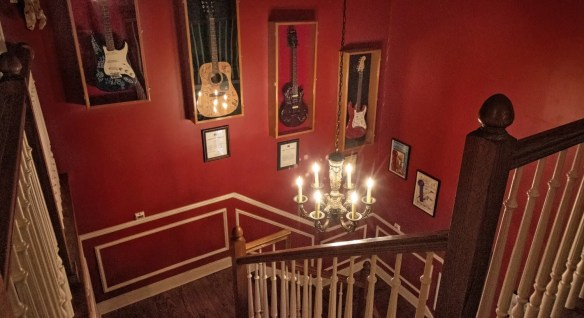 Dark wooden staircase with burgundy walls and vanilla trim and four wooden display cases with signed guitars hanging on the wall