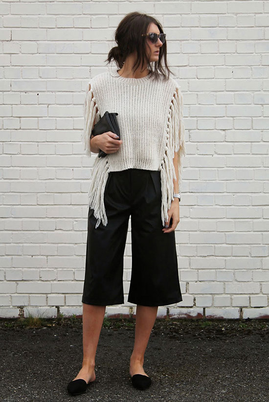 30 Chic Work Outfits to Wear this Summer: Fashion blogger 'Strut In Her Style' wearing a beige fringe sleeveless sweater, black wide leg crop pants, black suede flats, black sunglasses and a black clutch. Work outfits, summer work outfits, office wear, business casual, fashion, street style, womens fashion.