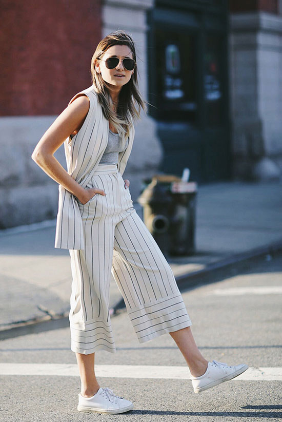 30 Chic Work Outfits to Wear this Summer: Fashion blogger 'We Wore What' wearing a stripe sleeveless jacket, a grey tank top, stripe crop wide leg pants, white casual sneakers and brown aviator sunglasses. Work outfits, summer work outfits, office wear, business casual, fashion, street style, womens fashion.
