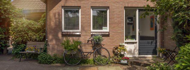 compositie van voorkant van de B&B en de fiets met bloemen