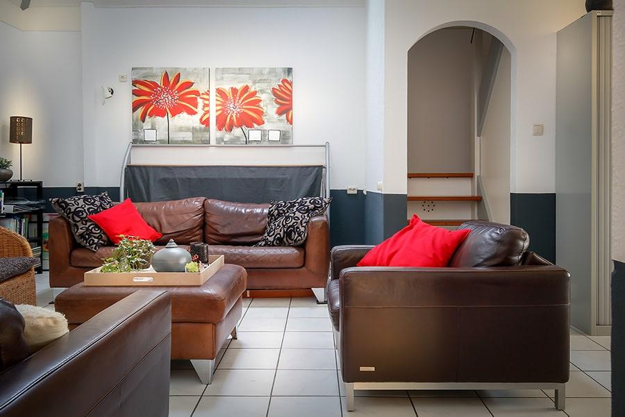 De bed & breakfast woonkamer met zicht op de bank en schilderijen van bloemen