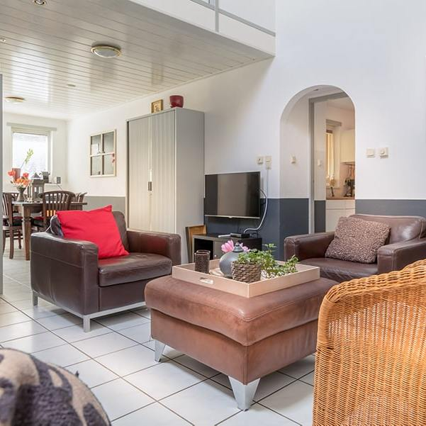 Woonkamer met bank, fauteuils en televisie met zicht op eetkamer
