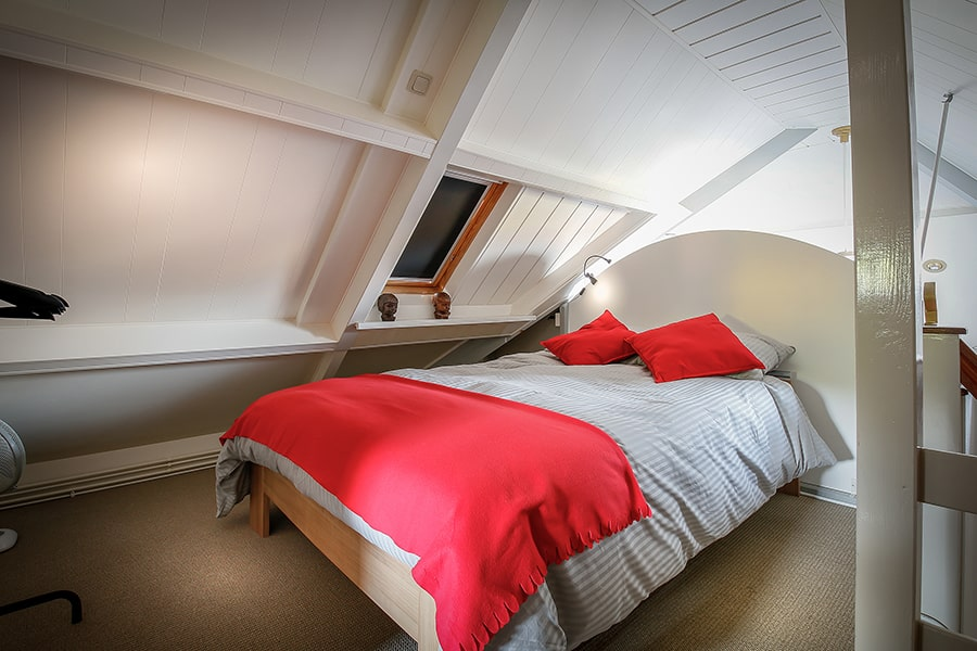De loft van de bed en breakfast met een opgemaakt tweepersoonbed