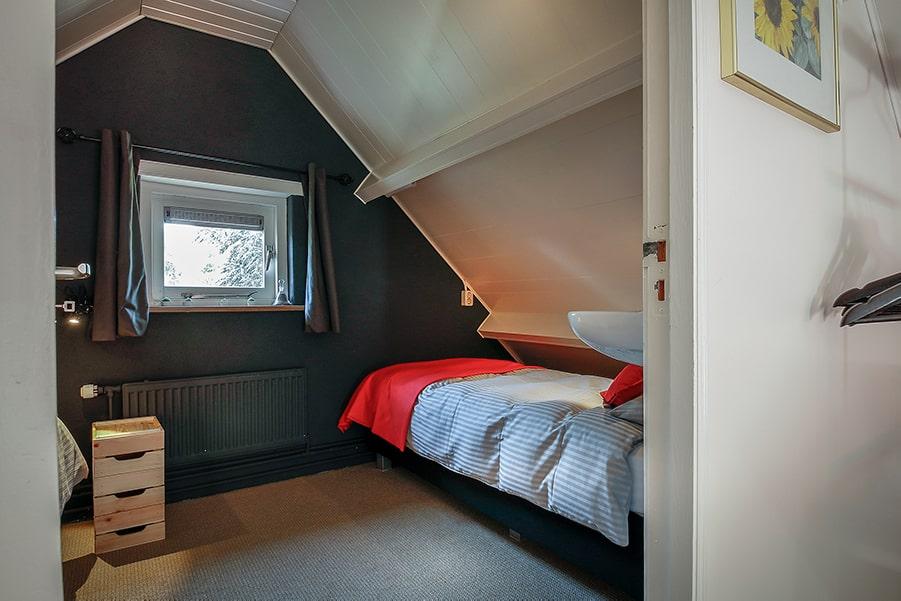 De slaapkamer van de B&B met een opgemaakt eenpersoonsbed