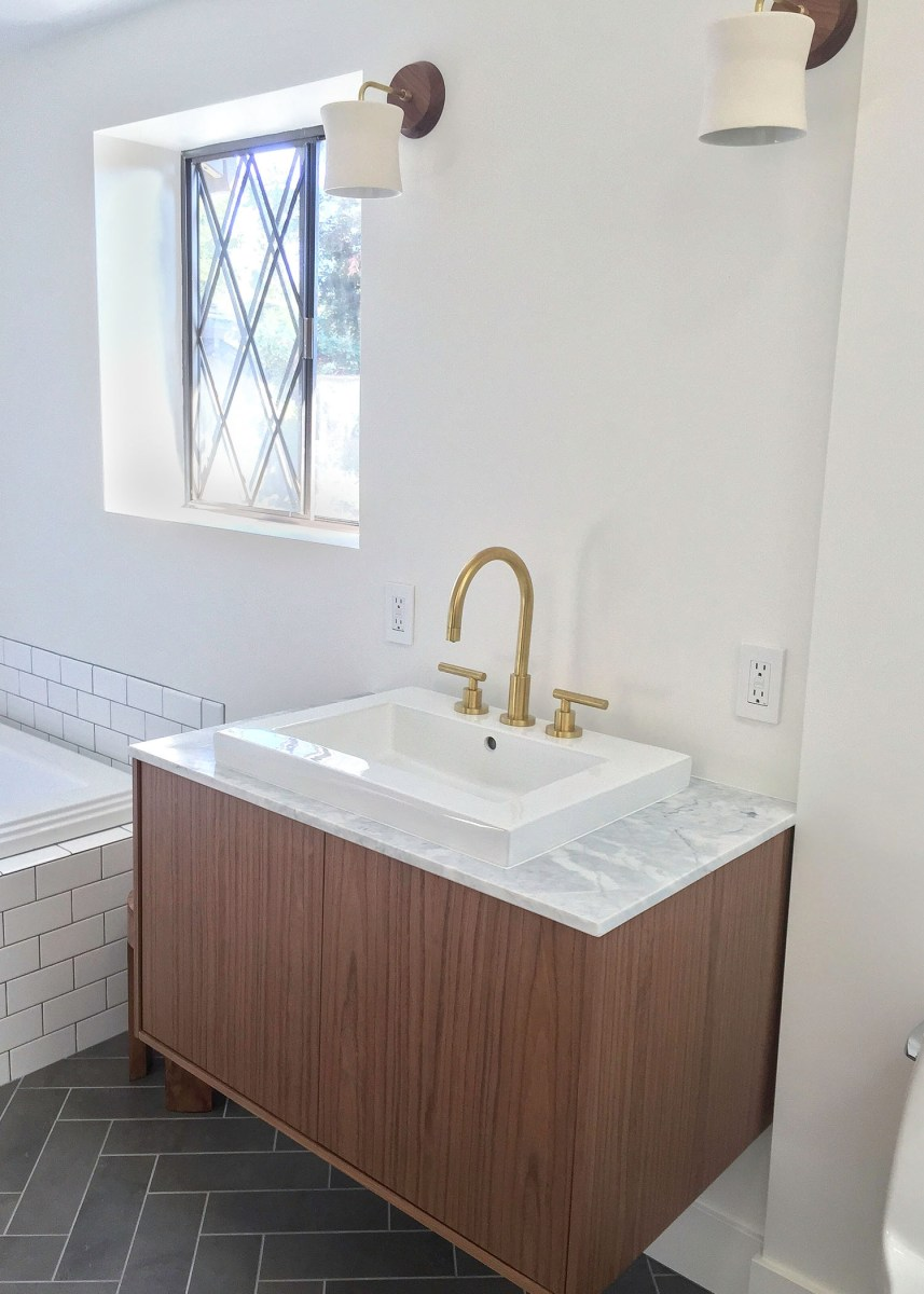 Beebout Design master bathroom remodel with herringbone tile floors, white subway tile, gray grout, walnut wood floating vanity, and brass fixtures.