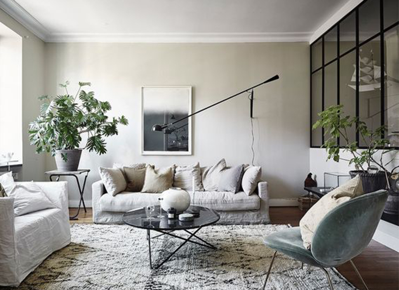Neutral living room design with slip-covered bench cushion sofa and large wall sconce.