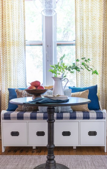 Broad Street Nook design with bench seating, buffalo check cushion, marigold yellow, pedestal table, bistro seating, and shaker chair by Beebout Design