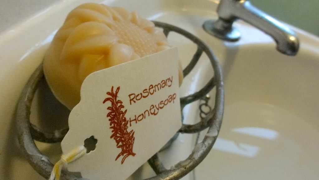 Rosemary Honeysoap on the basin with the tap in the background. The tag called 'Rosemary Honeysoap' is propped-up by the circular soap. #BeehiveYourself #Honeysoap