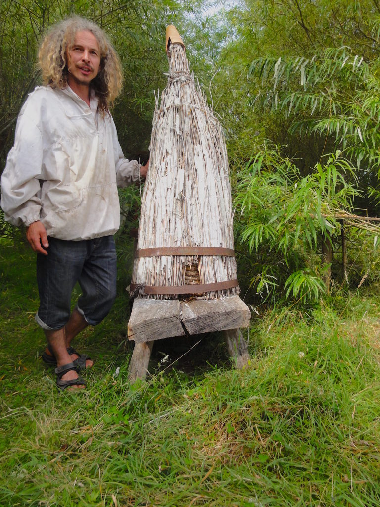 Chris Park standing next to a hackle which has a skep beneath it. The hackle gives weather protection to the straw skep. #BeehiveYourself, #WantageHoney, #SkepAndHackle, #Skep, Beehive Yourself, Wantage Honey, Chris Park