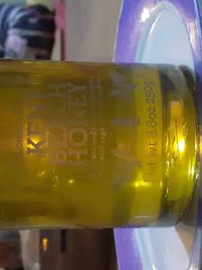 London Honey Company. Honey in contained in a bonta jar. Manifestation to glass. Plastic labels with white text. The label is difficult to see in the wrong light.