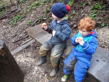 Boys playing outside in winter in muddy puddlesuits