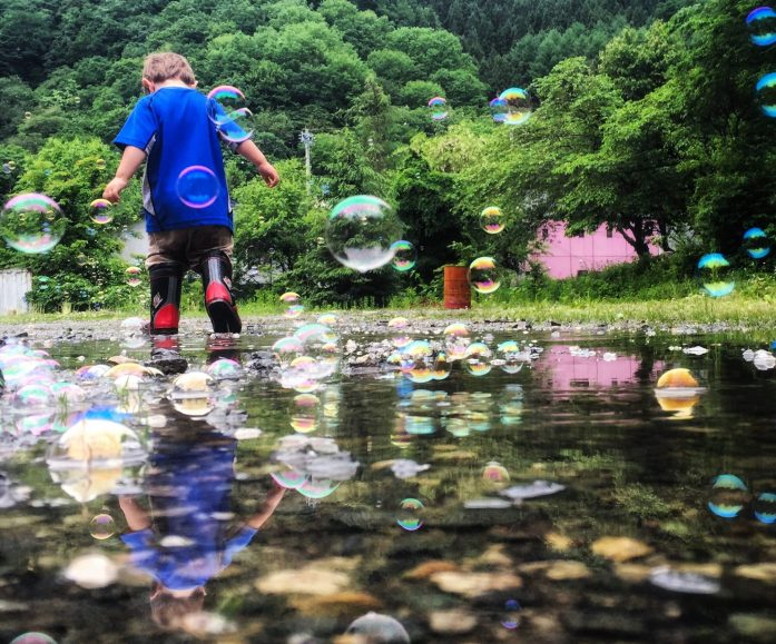 Appreciate. Child playing in puddles while surrounded by bubbles