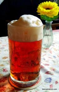 amber beer with huge head in mug