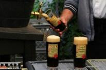 keg with brass tap filling dark beer