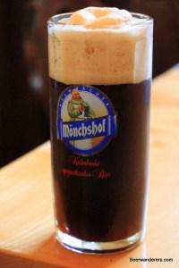 black beer with big tan head in mug