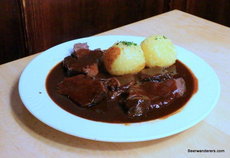 meat in dark sauce with dumplings