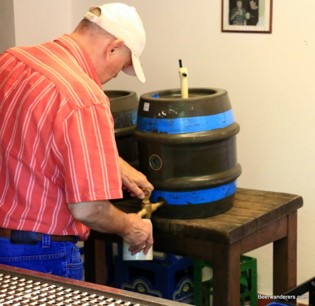 man pouring beer from barrel