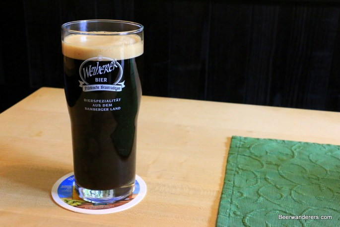 black beer in glass with tan head