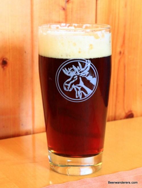 dark beer in glass with moose logo