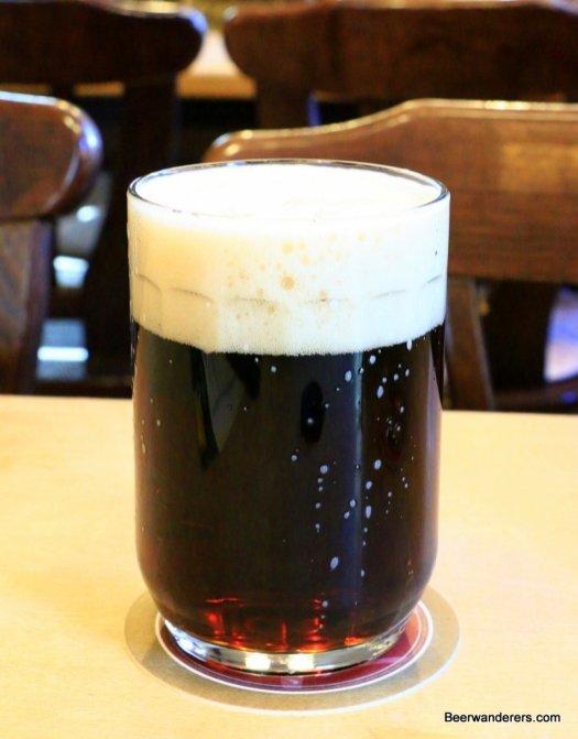 dark beer with big head in mug
