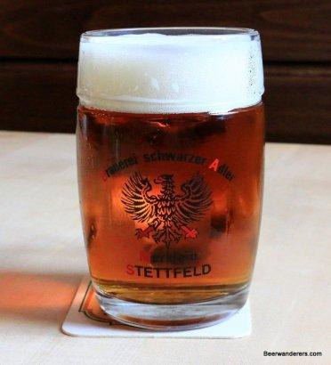 amber beer with big head in mug