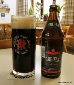 black beer in mug with bottle