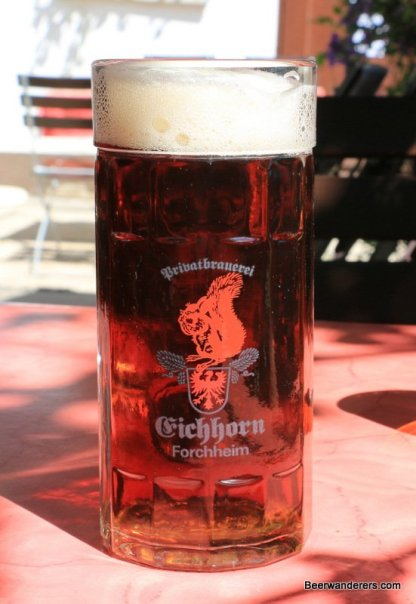 dark beer in glass with squirrel logo