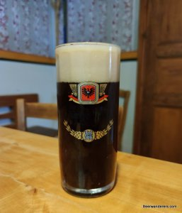 black beer in glass with huge head