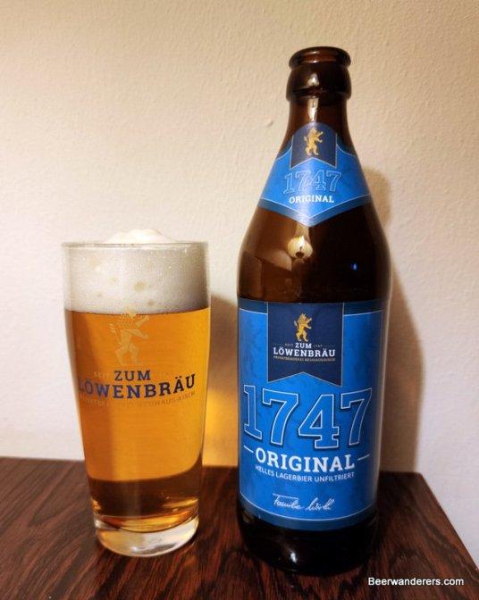 light golden beer in glass with bottle