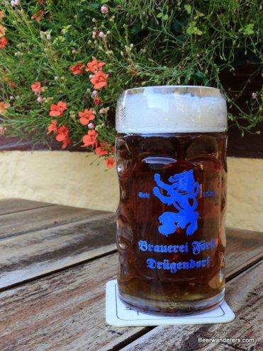 unfiltered dark beer in mug with logo