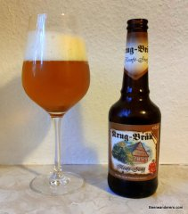 unfiltered amber beer in wine glass with bottle