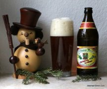 dark beer in glass with bottle and wooden snowman figure