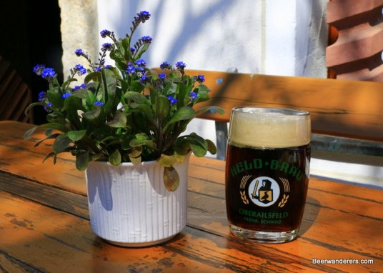 dark beer in mug with logo next to flowers