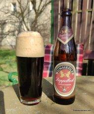 dark beer with huge head in glass with bottle