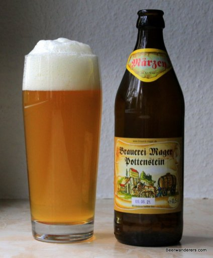 unfiltered golden beer in glass with bottle