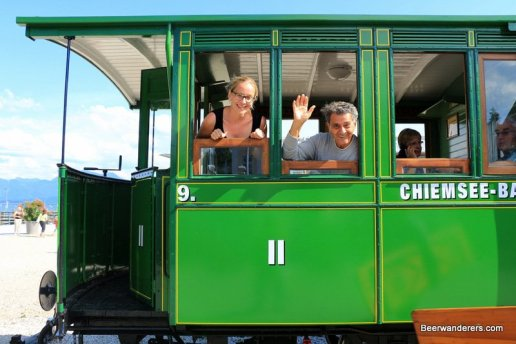 two people waving from steam train